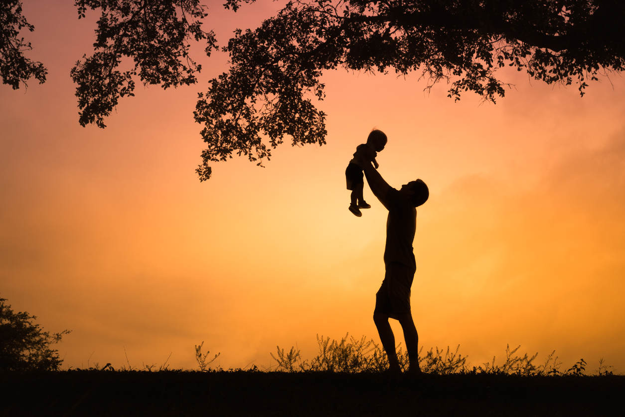 Father holding up son toward the sky